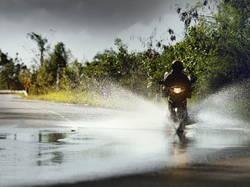 Riding a motorcycle through a water puddle in the road